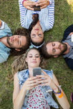 Happy friends lying on the grass Stock Image