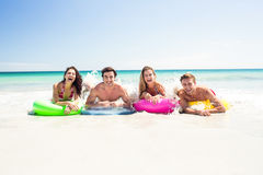 Happy friends lying on inflatable mattress above the water Stock Photography