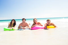 Happy friends lying on inflatable mattress above the water Stock Image