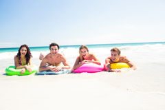 Happy friends lying on inflatable mattress above the water Royalty Free Stock Images
