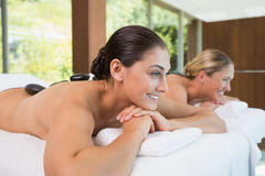 Happy friends lying on massage tables with hot stones on their backs Royalty Free Stock Photo