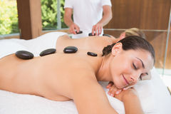 Happy friends lying on massage tables with hot stones on their backs Stock Image