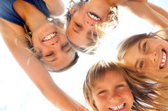 Happy friends making circle. Group of happy smiling girls playing together. From below view Stock Images