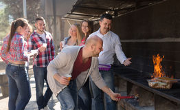 Happy friends making grill Royalty Free Stock Photo
