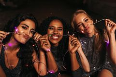 Happy friends making mustaches. With christmas lights royalty free stock photo