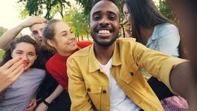 Happy friends are making online video call looking at camera, talking and laughing while African American man is holding. Device with camera during picnic in stock video