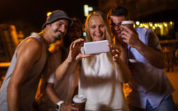 Happy friends making phone selfie at night. Group of excited friends taking selfie with smartphone at night. Focus on the mobile stock photography