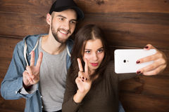 Happy friends making selfies isolated on wooden background Royalty Free Stock Photos