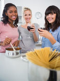 Happy friends making spaghetti dinner together and drinking red. Wine smiling at camera in kitchen Royalty Free Stock Photo