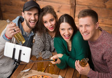 Happy friends making top view selfies in pizzeria Stock Photo