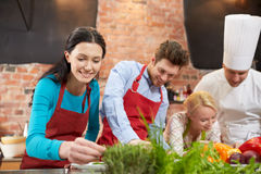 Happy friends and male chef cooking in kitchen Stock Photos