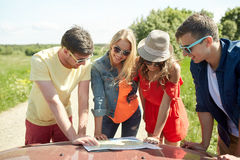 Happy friends with map and car searching location royalty free stock images