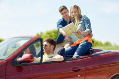 Happy friends with map driving in cabriolet car Stock Images