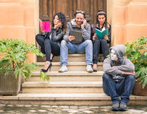Happy Friends with a masked outcast Person. Frontal view of happy friends during a university break not considering a masked outcast person royalty free stock photography