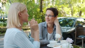 Happy friends ladies enjoying conversation in outdoor cafe on summer day. Happy friends mature ladies are enjoying casual conversation in outdoor cafe on summer stock video footage