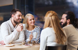 Happy friends meeting and drinking tea or coffee Royalty Free Stock Image