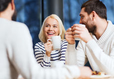 Happy friends meeting and drinking tea or coffee Royalty Free Stock Photo