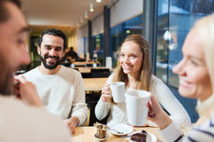 Happy friends meeting and drinking tea or coffee Stock Photos