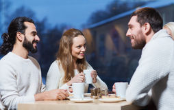 Happy friends meeting and drinking tea or coffee Royalty Free Stock Photos
