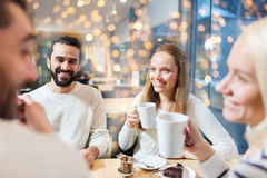 Happy friends meeting and drinking tea. People, leisure, communication, eating and drinking concept - happy friends meeting and drinking tea at cafe over Royalty Free Stock Photos