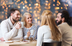 Happy friends meeting and drinking tea. People, leisure, communication, eating and drinking concept - happy friends meeting and drinking tea at cafe over Stock Photo