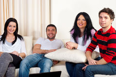 Happy friends meeting home. Happy four friends having a meeting in a house and sitting together on couch Stock Photo