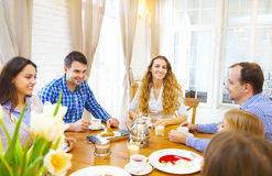 Happy friends meeting and talking and eating desserts on a table Stock Images