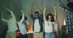 Happy friends men and women dancing having fun in dark apartment at night. Happy friends men and women in casual clothing are dancing having fun in dark stock video