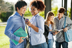 Happy Friends With Mobilephone And Book In Campus Stock Photos