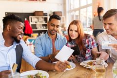 Happy friends with money paying bill at restaurant. Leisure, payment and people concept - happy friends with money and credit card paying bill for food at Stock Photos
