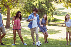 Happy friends in the park with football Stock Photos