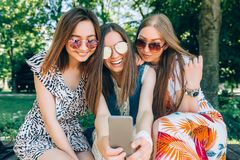 Happy friends in the park on a sunny day . Summer lifestyle portrait of three multiracial women enjoy nice day, wearing stock photo