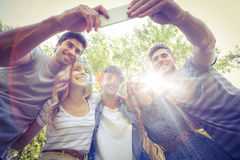 Happy friends in the park taking selfie. On a sunny day Stock Photography