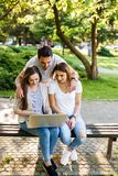 Three best friends in park enjoying and typing on laptop. Happy friends in park using laptop and enjoying the day Stock Images