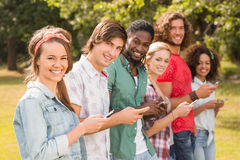 Happy friends in the park using their phones Royalty Free Stock Image