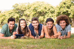 Happy friends in the park using their phones Royalty Free Stock Photos