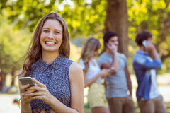 Happy friends in the park using their phones Stock Photo