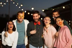 Happy friends with party props at rooftop royalty free stock image