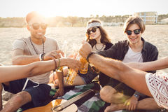 Happy friends partying on the beach. With drinks Royalty Free Stock Photos
