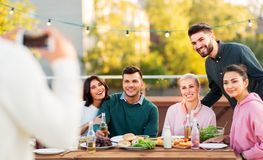 Happy friends photographing at rooftop party stock photography
