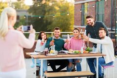 Happy friends photographing at rooftop party royalty free stock photo