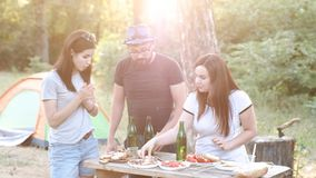 Happy friends on a picnic go up to the top of glass bottles, say a toast and laugh merrily. Happy friends at a picnic on the background of the sun`s rays, raise stock video footage