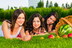 Happy friends on picnic on the lawn. Three  young happy girlfriends picnicking in the park  on green grass  and enjoying  fruit Stock Image