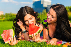 Happy friends on picnic on the lawn. Two  young happy girlfriends picnicking on the lawn  on green grass  and enjoying watermelon Royalty Free Stock Photos