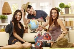 Happy friends planning holiday. Happy young roommates planning summer holiday, having globe, smiling Stock Images