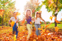 Happy friends play with colorful leaves in forest royalty free stock images