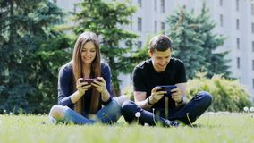 Happy friends play mobile game on smartphone, sitting on the grass in the park. Happy friends play mobile game on smartphone, man and woman sitting on the grass stock footage