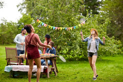 Happy friends playing badminton at summer garden. Leisure, holidays, people and sport concept - happy friends playing badminton or shuttlecock at summer garden Royalty Free Stock Photo