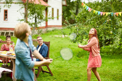 Happy friends playing badminton at summer garden. Leisure, holidays, people and sport concept - happy friends playing badminton or shuttlecock at summer garden Stock Image