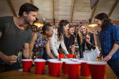 Happy friends playing beer pong game in bar Royalty Free Stock Photo